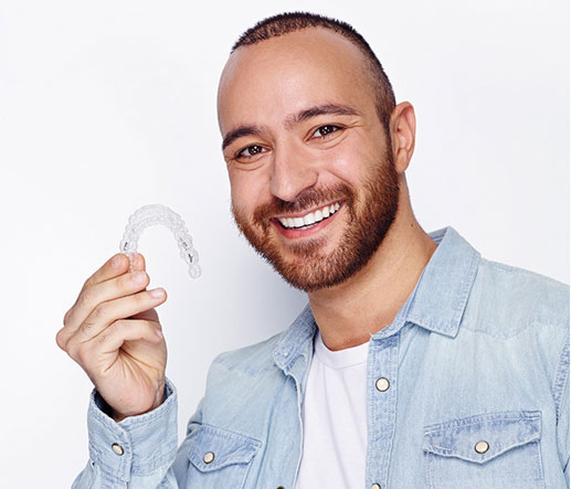 Man with a big smile holding up his invisalign brace